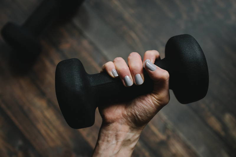 Woman with nice nails holding a weight