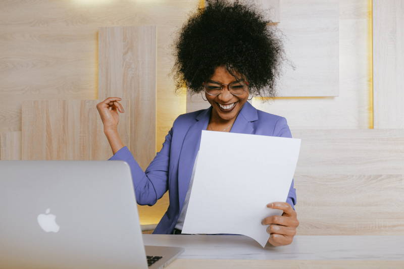 Woman smiling at a piece of paper