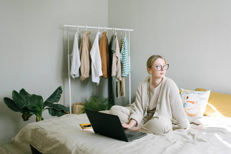 Woman working on her bed while staring out the window