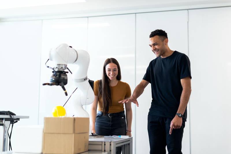 Man and woman looking at a robotic arm