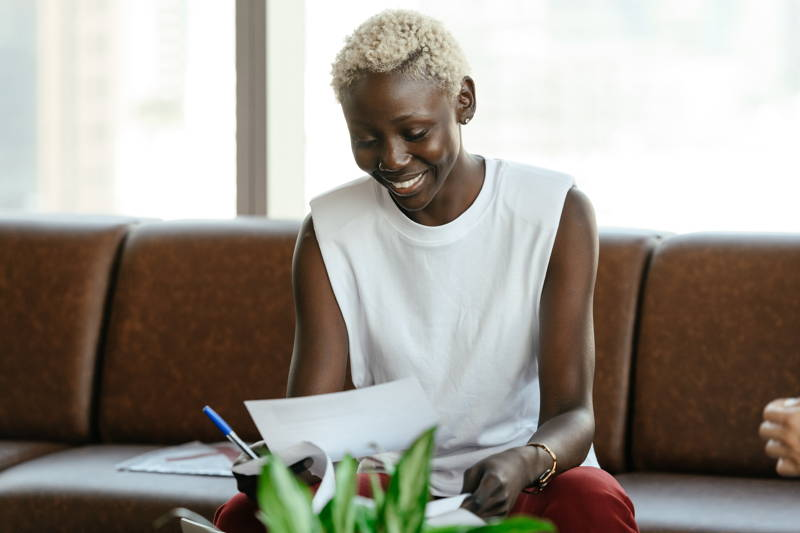 Woman smiling at a sheet of paper