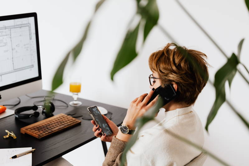 Woman talking on the phone while reading on another phone