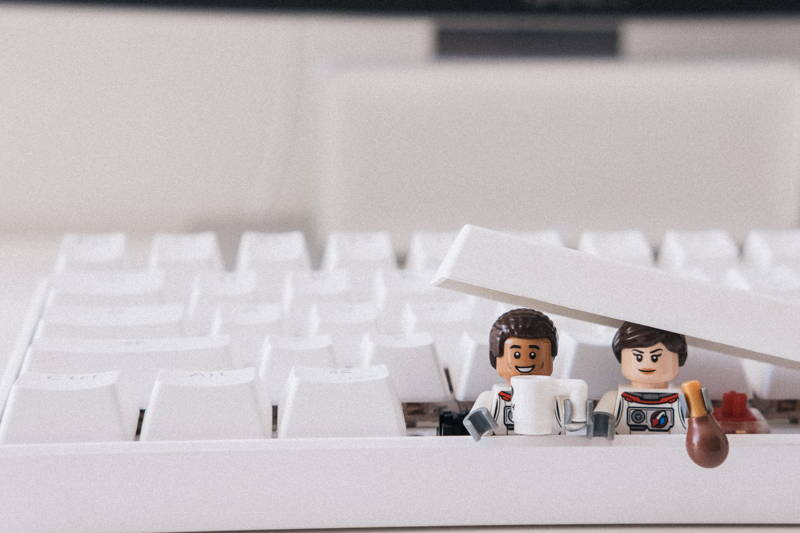 Lego characters sitting inside a computer keyboard
