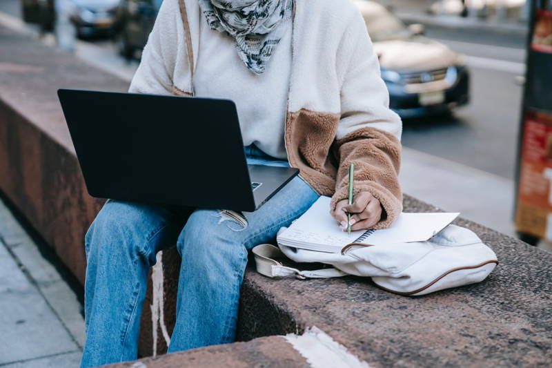 Woman writing on a notebook with her laptop in her lap