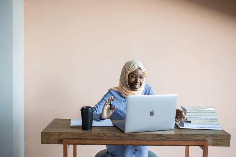 Woman waving at a computer