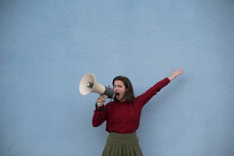 Woman yelling into a speaker