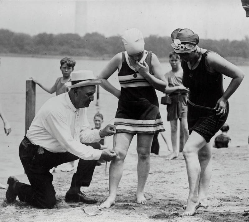 Historical photograph of a man measuring women's swimsuit lengths to ensure they are not six inches above their knees