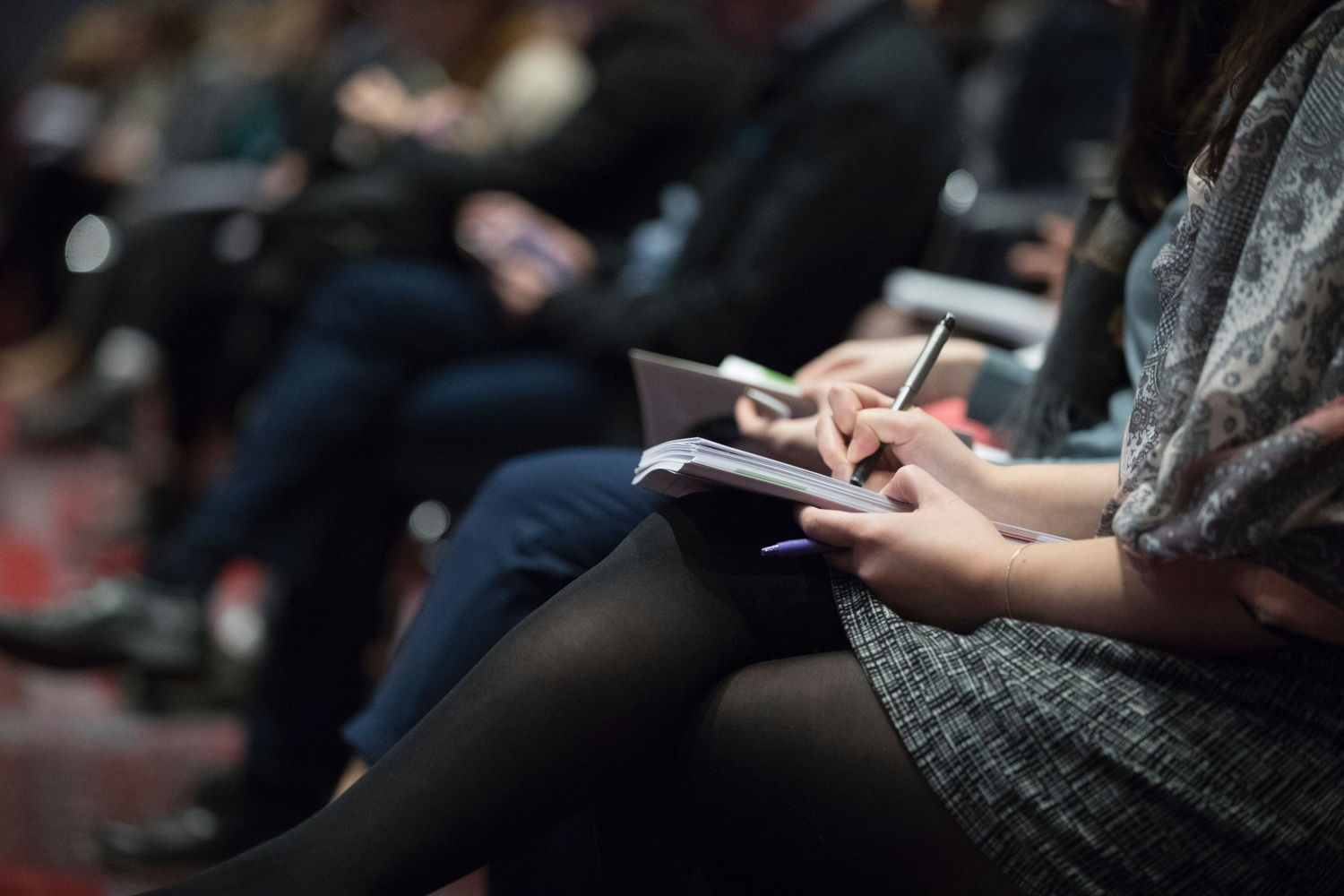 Women taking notes in a conference session