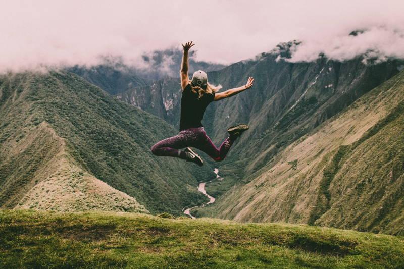 Woman jumping near mountains