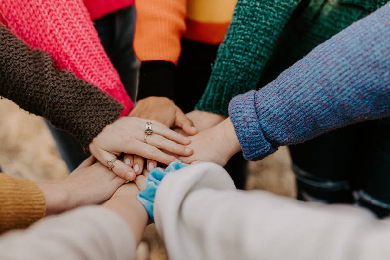 women in a circle touching hands