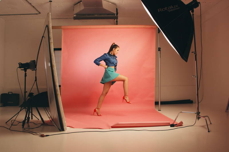 Woman posing on the set of a photoshoot with one foot raised in front of a pink backdrop.