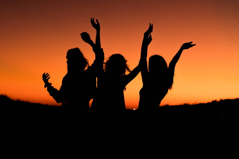 Women dancing in front of a sunset.