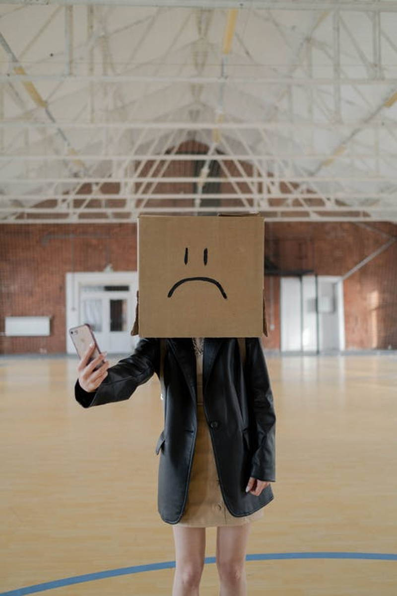 A woman wearing a box on her head with a frown face