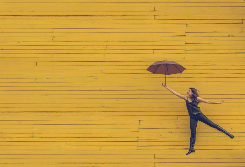 Woman jumping in front of a yellow wall with an umbrella