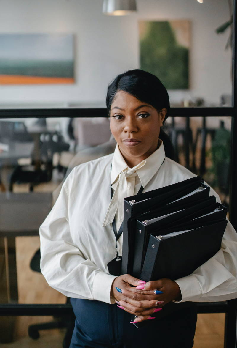 Woman holding binders and looking directly at the camera