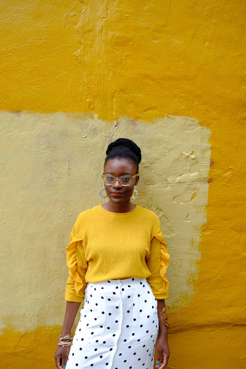 Woman in yellow crew neck leaning against a wall