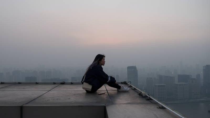 Women sitting atop a skyscraper
