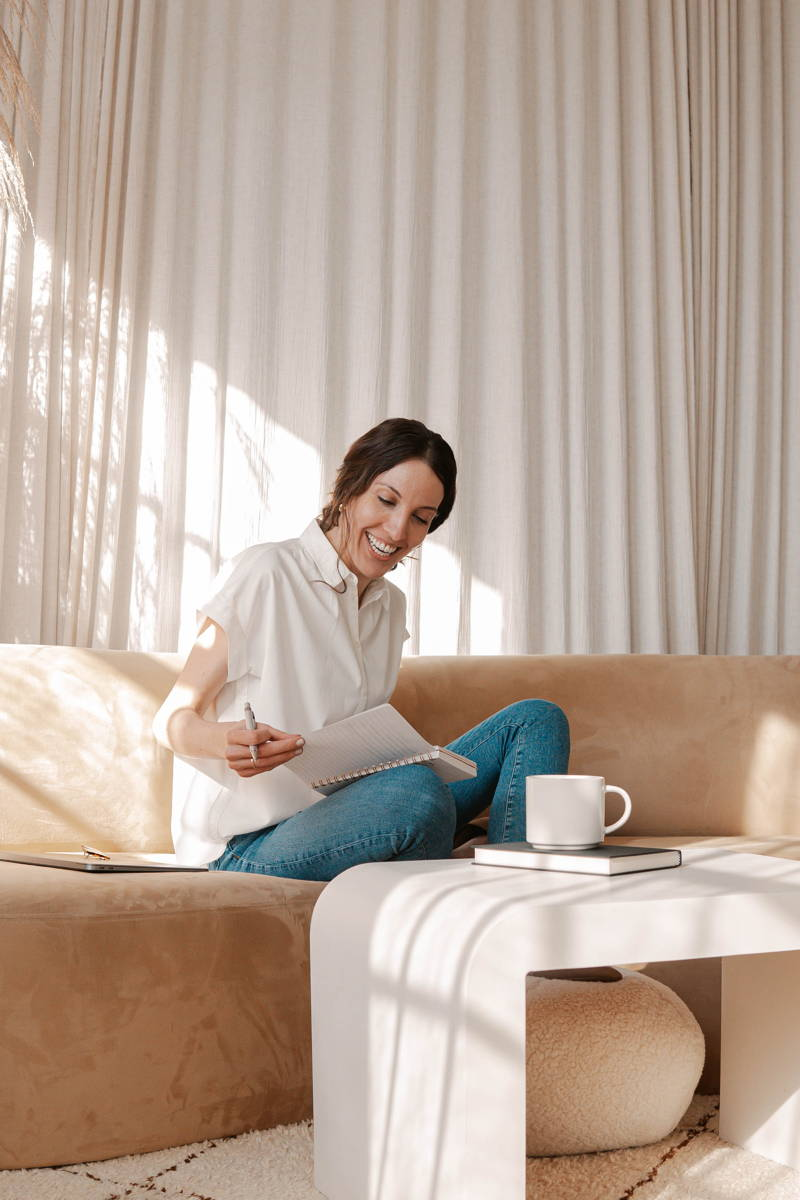 Woman looking through papers while sitting on a couch