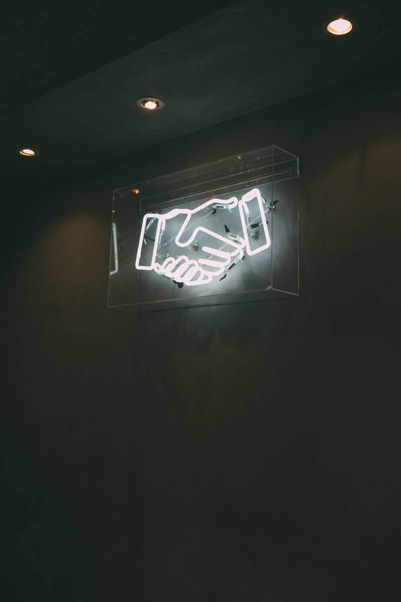 A neon light of a handshake