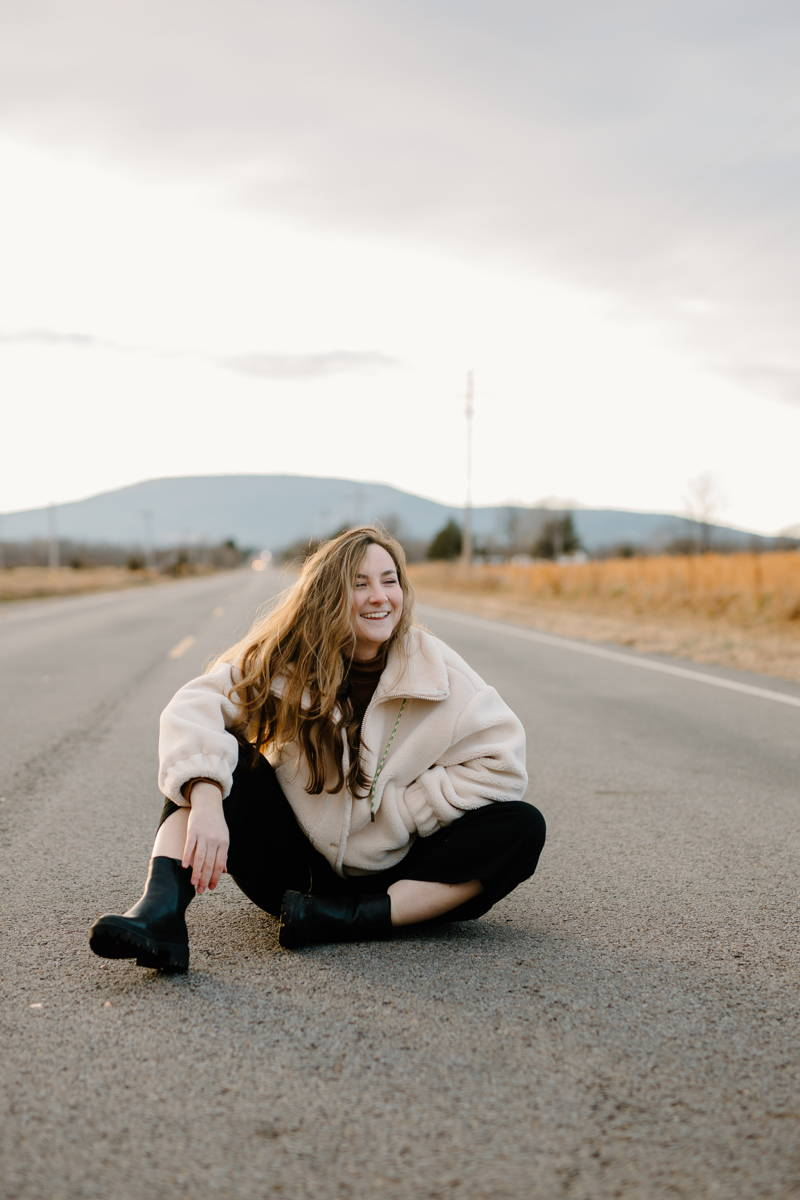 Woman sitting in the middle of the road and laughing