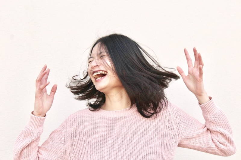 Woman in pink sweater laughing