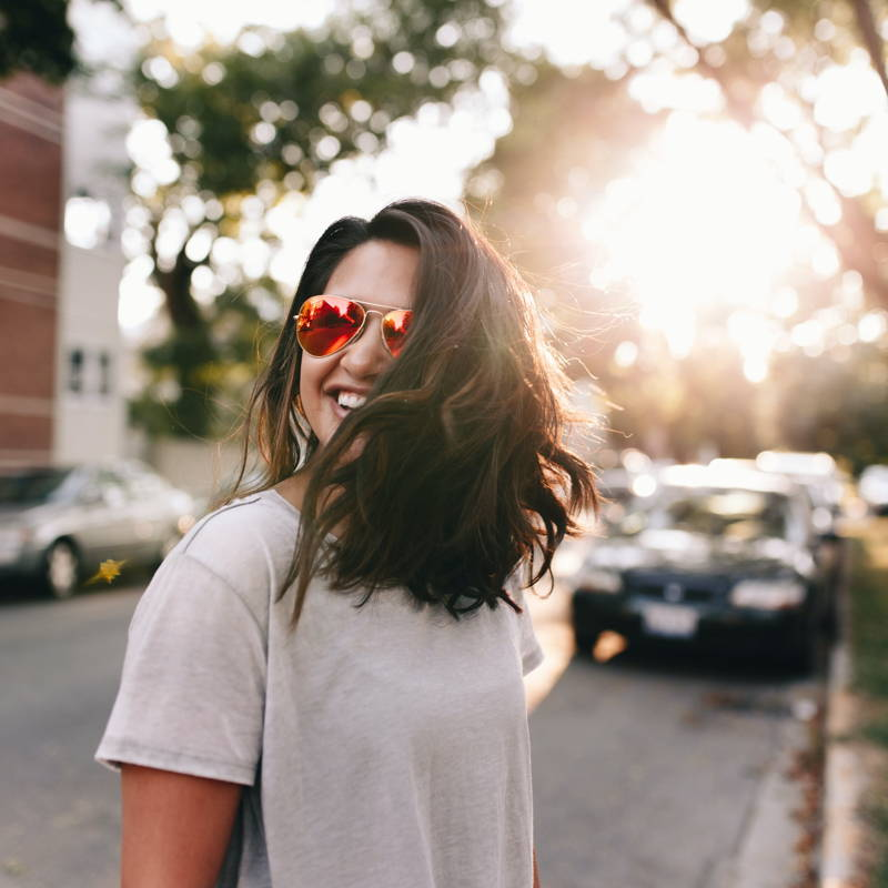Woman in sunglasses laughing.