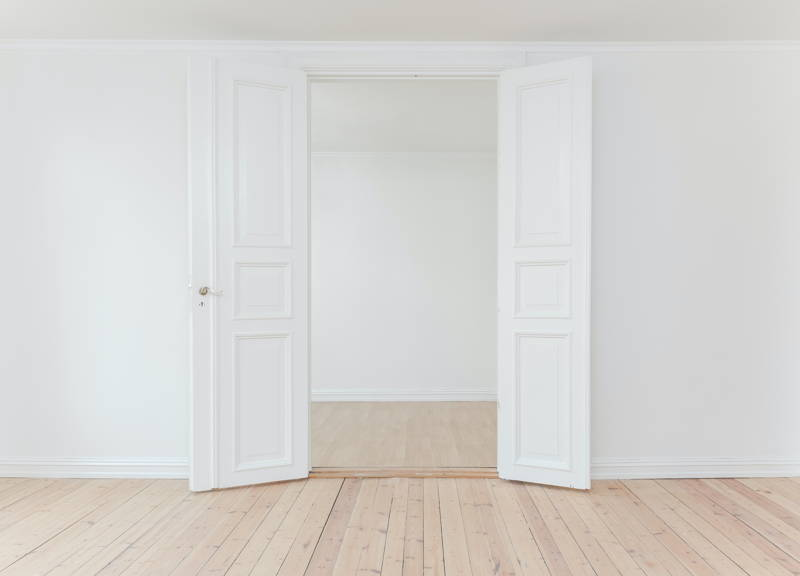 Two open French doors in a very white room