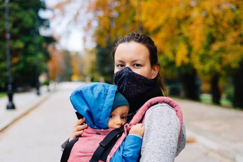 Masked mom holding her child
